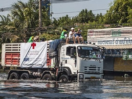 men sitting on a red cross truck going through a river