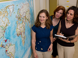 Three professors looking at a world map