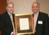 Chip White presents Joe Mello (IE 1980) with the Hill Society Award for his leadership in the healthcare industry
