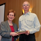 Susan Albin, INFORMS president, presents plaque to Bill Cook.