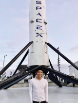 Daniel Kurniawan in front of the rocket at SpaceX