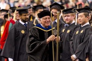 George Nemhauser carries the ceremonial mace at the Fall 2015 Commencement for Ph.D. and master's graduates. The mace, with its three brass rods, symbolizes Georgia Tech's mission and its three primary components: education, research, and service.