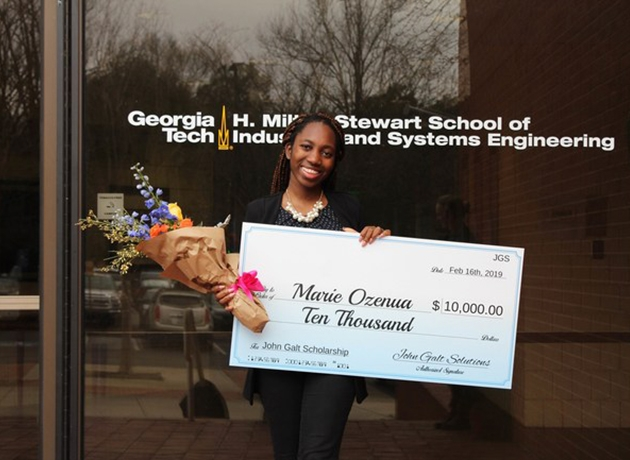 Marie Ozenua holding a check in front of ISyE