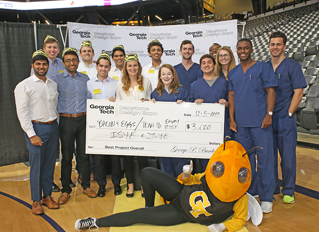Senior Design Winners standing with Buzz and a check